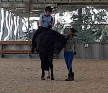 Cynthia showing Sarah how to have her reins